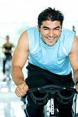 Mann lächelnd während des Fahrens In einem Fitness-Studio