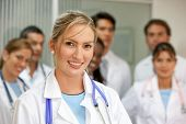 female doctor smiling in a hospital with her team behind