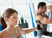 Beautiful gym woman exercising on a machine