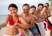 Grupo de amigos na praia puxando uma corda