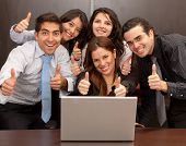 Business group with thumbs up in an office