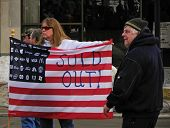 """Angry Woman Carries """"Sold Out"""" flag"""