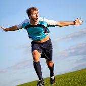 Footballer running on the field celebrating a goal