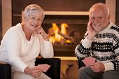 Portrait of happy senior couple playing cards at home in front of cosy fireplace, smiling at camera.?
