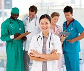 foto of medical staff  - Smiling female doctor with her team in the background - JPG