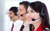 Happy co-workers with headsets on in call center
