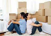 Tired couple relaxing sitting on the floor while moving house