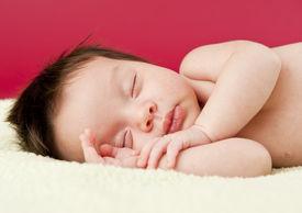 stock photo of sleeping baby  - Newborn baby eyes closed sleeping on its side - JPG