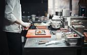 Restaurant Chef Cook Preparing Salmon Filet Flambe. Focus Is On The Salmon, Burner And Cook`s Hand.  poster