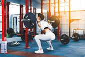 Back View Young Adult Girl Doing Squat In Gym With Barbell. Fit Woman In Great Shape. The Developmen poster