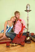 Couple Sit On Pillow And Smoke Hookah