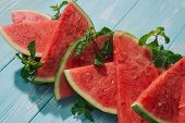 Slices Of Watermelon On Blue Wooden Desk. poster