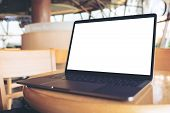 Mockup Image Of Computer Laptop With Blank White Desktop Screen On Wooden Table In Cafe poster