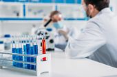 Selective Focus Of Tubes With Reagents And Scientists At Workplace In Lab poster