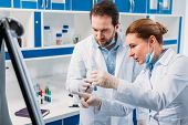 Scientist In White Coats Near Board For Notes Having Discussion During Work In Lab poster