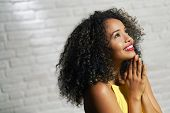 Portrait Of Happy Latina Woman Smiling And Saying Prayer. Black Girl Looking Up While Praying. poster
