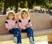 Twin Girls On Park Bench