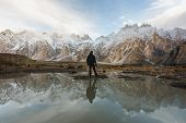 Young Photographer Looking At Passu Cathedral Mountain In Pakistan And Reflection On The Water. Moun poster