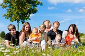 Family and multi-generation - mother, father, children and grandmother having fun on meadow in summe