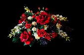stock photo of flower arrangement  - An arrangement of silk flowers against a black background - JPG