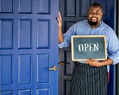 A cheerful small business owner with open sign poster