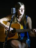 Photo Of A Vintage Microphone And Blurred Woman Playing Acoustic Guitar In The Background. Focus On  poster