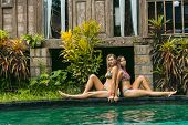 Beautiful Young Women In Swimwear Resting Near Swimming Pool And Looking At Camera poster