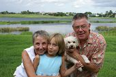 Senior Couple With Grandchild And Family Pet
