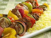 picture of kababs  - Juicy beef kebabs with bell peppers onions zucchini and cherry tomatoes. Accompanied by a bed of saffron flavored basmati rice.