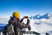 woman traveler in Swiss alps Jungfrau region taking pictures poster