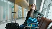 Young Brunette Woman In Glasses Is Waiting Her Flight In Airport Sitting In Hall With Her Luggage. S poster