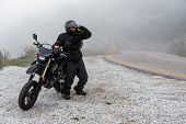 Rider Trying To See Through The Fog On An Adventure Ride On The Mountains poster