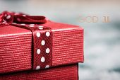 closeup of a red gift box, tied with a nice red ribbon, on the snow and the text merry christmas wri poster