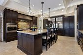 stock photo of granite  - Luxury kitchen in upscale home with dark wood cabinetry - JPG