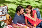 Woman putting food into her friends mouth as they lie on a blanket with a picnic basket,food and flo