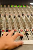 Sound Engineer's Hand Moving On Sound Mixing Board