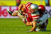 VIENNA, AUSTRIA - JUNE 5 RB Andrej Kliman (#3 Austria) is tackled by DB Bobby Short (#43 Rose Hulman