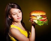 Slim woman holding hamburger.