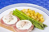 stock photo of rutabaga  - Two poached eggs on thin slices of Pancetta over toasted wholewheat bread served with roasted asparagus and Rutabaga - JPG