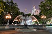 The Municipal Building towers over the fountain in City Hall Park in Lower Manhattan New York CIty.