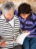 Grandmother reading a story to her grandson at home