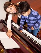 Young boy taking piano lessons at home