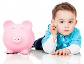 Boy saving money in a piggybank - isolated over a white background
