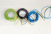 Electric cable coil in three colors black blue and green yellow earth ground
