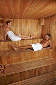 Happy man and woman sitting together in a wooden sauna