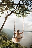 Woman Swinging Outdoors Over Amazing Mountain, Jungle And Lake View Over A Cliff In Bali Wanagiri Hi poster