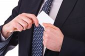 Businessman putting blank card in his pocket.