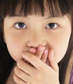 Scared little girl covering mouth with hand