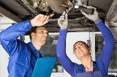 Mechanics Repairing A Car On Hydraulic Ramp