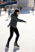 Slim Young Woman Ice Skating On An Ice Rink
